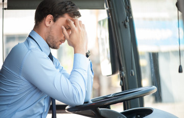 Handsome man is sitting at steering wheel of the bus. He is touching his head with frustration. The man has a terrible headache