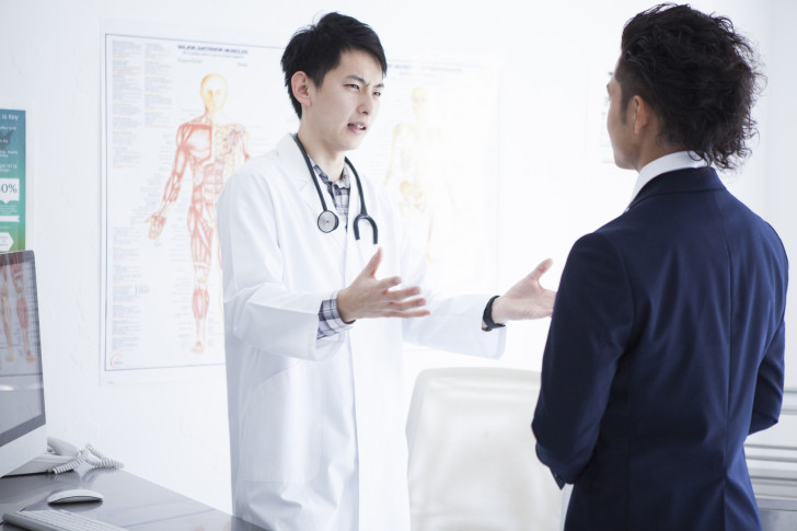 A businessman and a doctor are talking in the diagnosis room