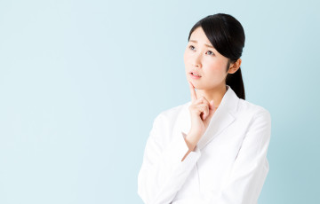 portrait of young asian nurse isolated on blue background