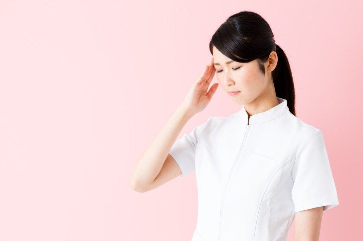 portrait of young asian nurse isolated on pink background